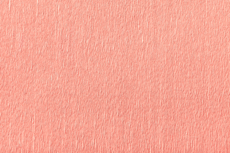 Textural of pink background of wavy corrugated paper, closeup. Structure of wrinkled crepe light coral cardboard macro.