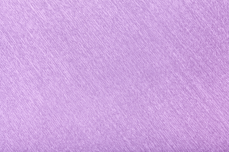 Textural of violet background of wavy corrugated paper, closeup. Structure of wrinkled crepe light lilac cardboard macro.