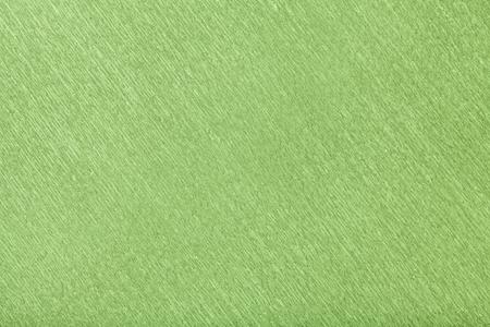 Textural of green background of wavy corrugated paper, closeup. Structure of wrinkled crepe light olive cardboard macro.
