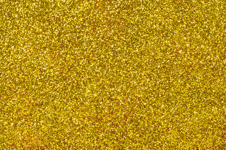 Golden sparkling background from small sequins, closeup. Brilliant shiny backdrop from textile. Shimmer yellow paper