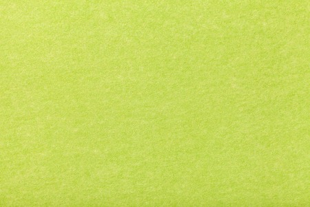 Light green matte background of suede fabric, closeup. Velvet texture of seamless olive woolen felt.