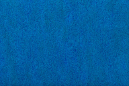 Navy blue matte background of suede fabric, closeup. Velvet texture of seamless denim woolen felt.