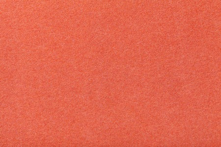Dark orange matte background of suede fabric, closeup. Velvet texture of seamless red woolen felt. Banque d'images