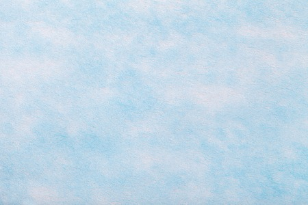 Construction of a light blue background with white spots of felt fabric, closeup. Texture of sky woolen matt textile. Cloth backdrop.