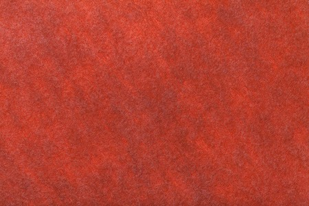 Dark orange matte background of suede fabric, closeup. Velvet texture of seamless bright red woolen felt.
