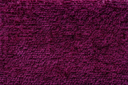 Dark purple background of soft, fleecy cloth. Texture of wine fluffy textile closeup.
