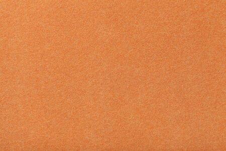 Light orange matte background of suede fabric, closeup. Velvet texture of seamless ginger woolen felt.