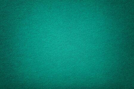 Dark turquoise matte background of suede fabric, closeup. Velvet texture of seamless green woolen felt with vignette.