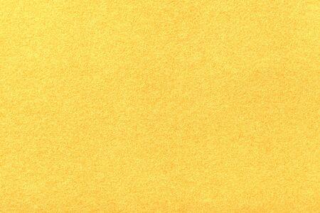 Hellgelber matter Hintergrund aus Wildleder, Nahaufnahme. Samttextur aus nahtlosem goldenem Wollfilz.