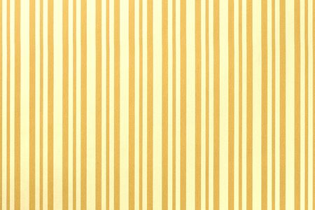 Light yellow and golden background from wrapping paper with a pattern of line closeup. Texture of holiday striped paper surface. Backdrop of orange textile.