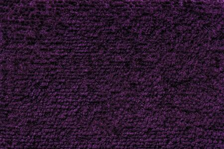Dark purple background of soft, fleecy cloth. Texture of violet fluffy textile closeup. Banque d'images