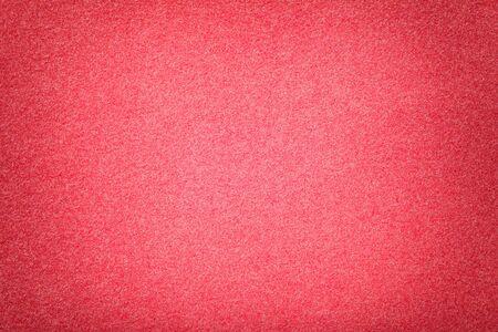 Light red matte background of suede fabric, closeup. Velvet texture of seamless pink woolen felt with vignette.