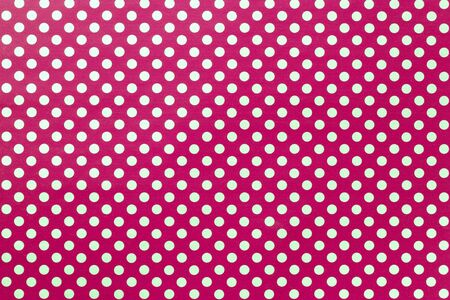 Dark red background from wrapping paper with a pattern of golden polka dot closeup. Texture of purple holiday dotted paper surface. Backdrop of wine textile.