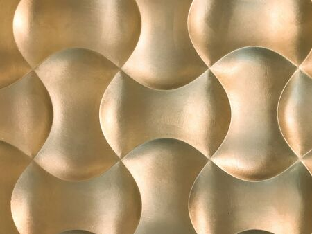 Golden 3D interior decorative wall panel with unusual geometric shape. Metallic yellow background with pattern. Abstract texture.