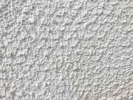 Texture decorative white plaster imitating the old peeling wall. Obsolete ivory cracked background, closeup.