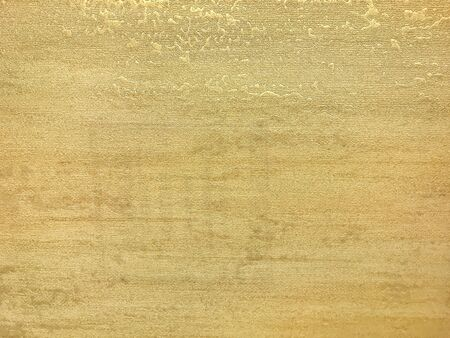 Texture of light yellow wallpaper with a curly glossy pattern. Golden paper surface, structure closeup.