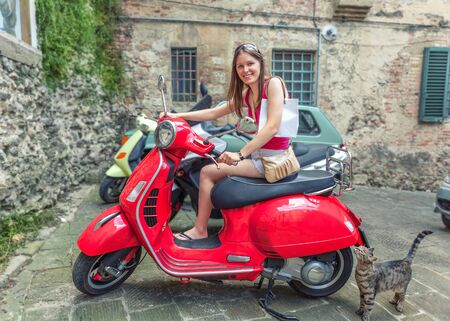 Young beautiful girl rides a red motor scooter Vespa through the streets of Rome, Italy. Happy travel vacation.