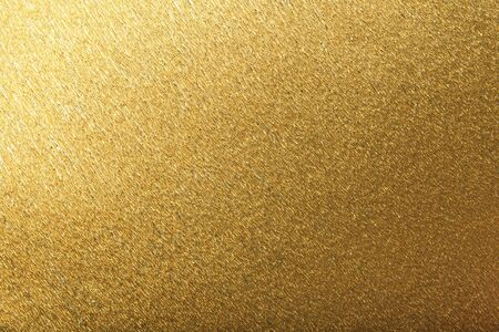 Textural of golden foil background of wavy corrugated paper, closeup. Structure of metallic wrinkled crepe yellow cardboard, macro. Banco de Imagens