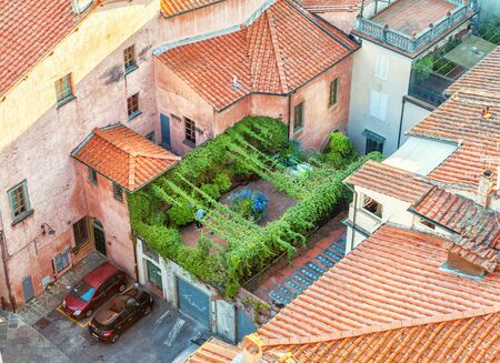 Lucca, Italy - August 18, 2013: Secluded roof garden of an old Italian building. Urban rooftop from medieval Italy.