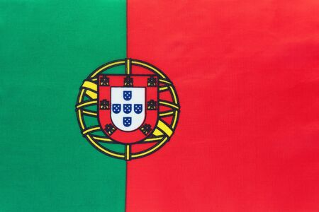 Portugal national fabric flag with emblem, textile background. Symbol of international world european country. State official sign.