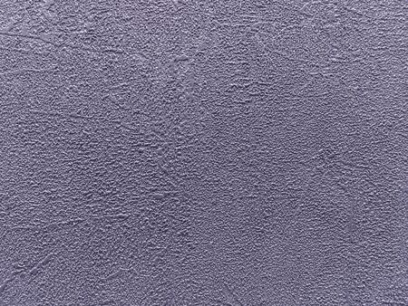 Structure of purple abstract background in the form of a rough patchy plaster of violet color. Texture of lavender decorative shiny wallpaper, closeup.