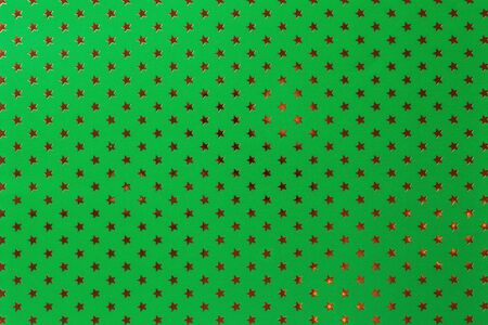 Dark green background from metal foil paper with a pattern of sparkling golden stars, closeup. Texture of emerald metallized wrapping holiday paper surface.