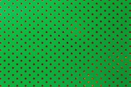 Fond vert foncé de papier d'aluminium avec un motif d'étoiles dorées scintillantes, gros plan. Texture de la surface du papier de vacances d'emballage métallisé émeraude. Banque d'images