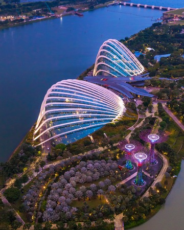 Singapore - 07 July 2018: Aerial night view of the botanical garden, Gardens by the Bay in Singapore. Supertrees Marina Bay. Top view of the glass greenhouse