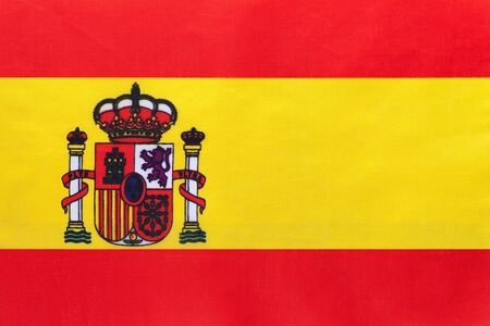 Spain national fabric flag with emblem, textile background. Symbol of international world european country. State official spanish sign.