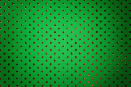 Dark green background from metal foil paper with a pattern of sparkling golden stars, closeup. Texture of emerald metallized wrapping holiday paper surface with vignette.