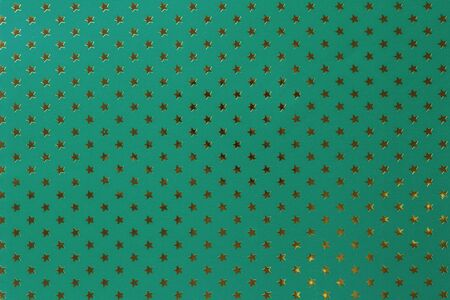 Dark green background from metal foil paper with a pattern of sparkling golden stars, closeup. Texture of turquoise metallized wrapping holiday paper surface.