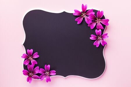 Black wooden chalkboard with purple flowers on pink paper background with copy space. Floral greeting card. flat lay.