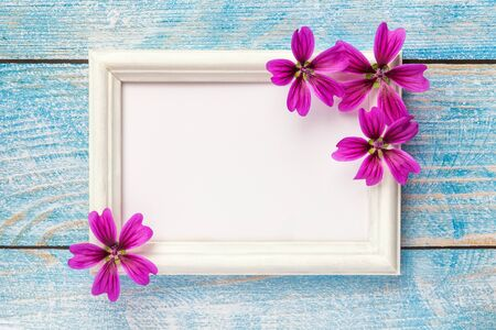 White wooden photo frame with purple flowers on old blue shabby wooden background with copy space. Floral greeting card. flat lay.