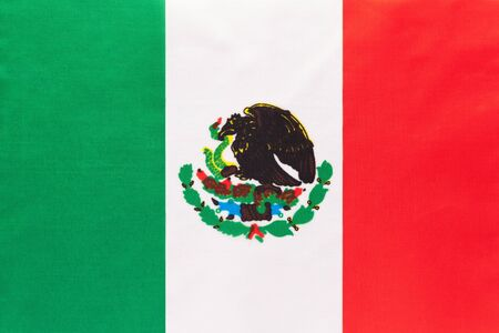 Mexico national fabric flag with emblem, textile background. Symbol of international world North America country. State official mexican sign.