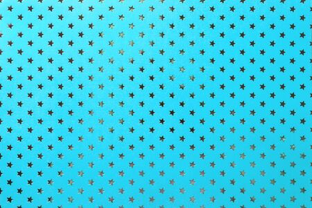 Light blue background from metal foil paper with a pattern of sparkling silver stars, closeup. Texture of turquoise metallized wrapping holiday paper surface.
