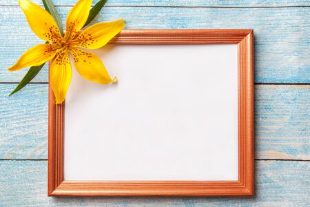 Brown wooden photo frame with yellow flowers lily on old blue shabby background with copy space. Floral greeting card, flat lay.