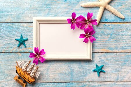 White wooden photo frame with purple flowers on blue old shabby background with copy space. Vacation greeting card with sea stars, seashell and ship. Travel concept.