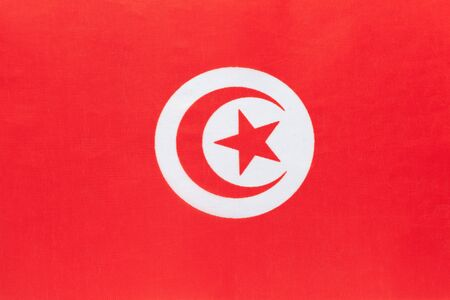 Tunisia national fabric flag with emblem, textile background. Symbol of international world african country. State official tunisian sign.