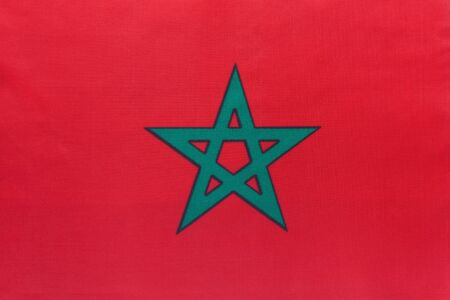 Morocco national fabric flag with emblem, textile background. Symbol of international world african country. State official moroccan sign.