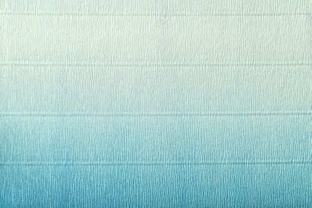 Texture of corrugated light blue and white paper with vertical gradient, macro. Striped pattern of turquoise cardboard background, closeup.