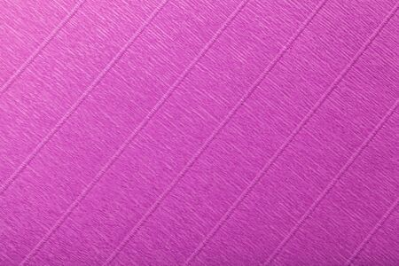 Textural of purple background of wavy corrugated paper, closeup. Structure of wrinkled crepe magenta cardboard macro. Фото со стока