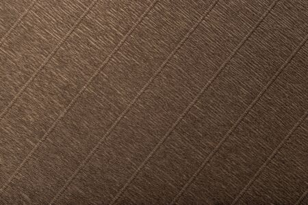 Textural of bronze background of wavy corrugated paper, closeup. Structure of wrinkled crepe dark brown cardboard macro. Фото со стока