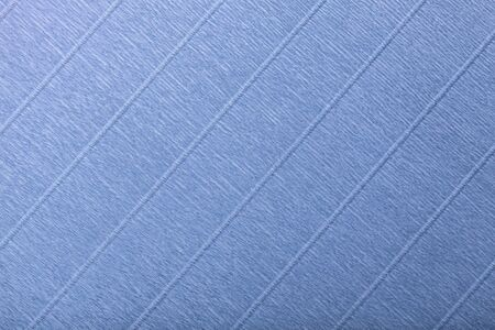 Textural of navy blue background of wavy corrugated paper, closeup. Structure of wrinkled crepe light denim cardboard macro.