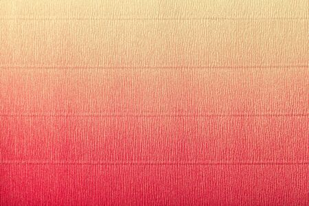 Texture of corrugated light red and yellow paper with vertical gradient, macro. Striped pattern of coral cardboard background, closeup.