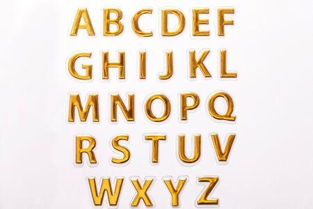 Set of shiny golden glossy letters, isolated on white background. Symbol of english alphabet abc.