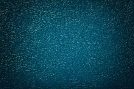 Dark navy blue leather texture background, closeup. Turquoise cracked backdrop from wrinkle skin, structure of textile with vignette. Фото со стока