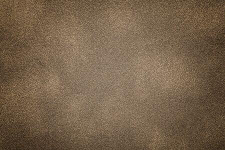 Background of light bronze suede fabric closeup. Velvet matt texture of brown nubuck textile with vignette.