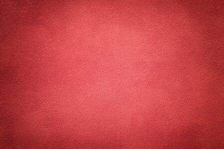 Background of light red suede fabric closeup. Velvet matt texture of wine nubuck textile with vignette.
