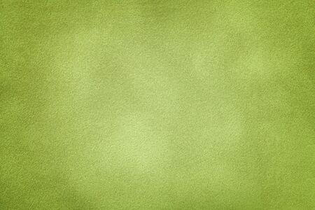 Background of light green suede fabric closeup. Velvet matt texture of olive nubuck textile with vignette.