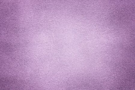 Background of light violet suede fabric closeup. Velvet matt texture of lilac nubuck textile with vignette.